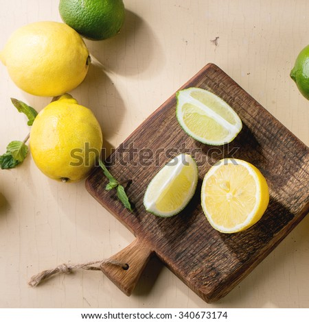 Heap of whole and sliced lemons and limes on little wooden cutting board over wooden background. Rustic sun light. Top view. Square image - stock photo