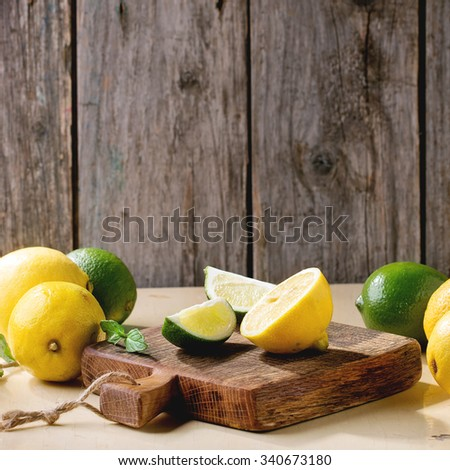 Heap of whole and sliced lemons and limes on little wooden cutting board over wooden background. Rustic sun light. Square image - stock photo