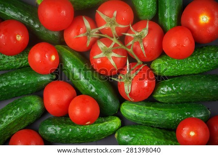Heap of whole wet tomatoes and cucumbers. Top view point, full frame. - stock photo