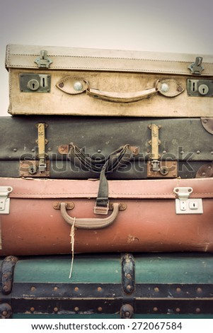 Heap of worn vintage leather suitcases in various colors - stock photo