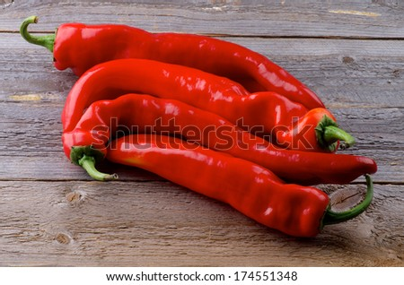 Heap Raw Ripe Red Ramiro Peppers isolated on Rustic Wooden background