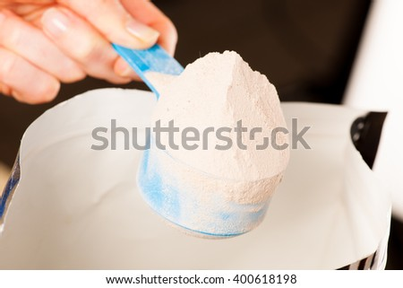 Heaped measuring scoop of whey protein powder with chocolate flavour.