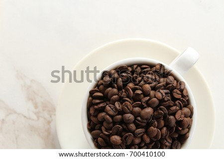 Heaping coffee beans in a white cup and saucer against white marble copy space.