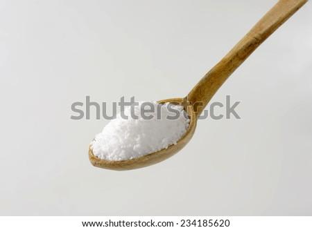 heaping wooden spoon of sea salt - stock photo