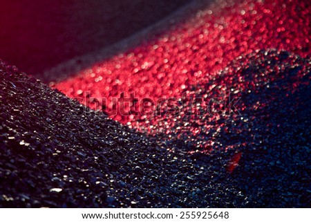 Heaps of coal in the red light - stock photo