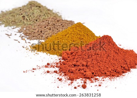 Heaps of different dry spices on a white
