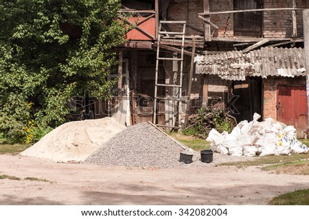 heaps of sand and gravel near the dilapidated house - stock photo
