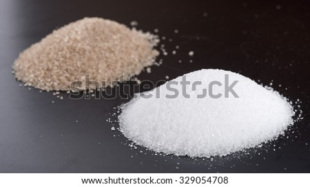 Heaps of white and brown crystal sugar, on black background