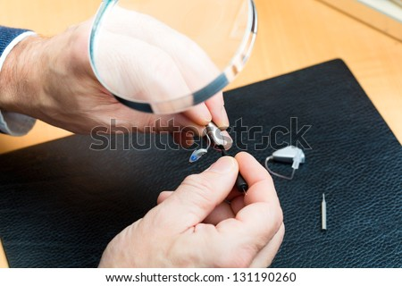 hearing aid acoustician at work, he is working on a hearing aid for hearing impaired persons - stock photo