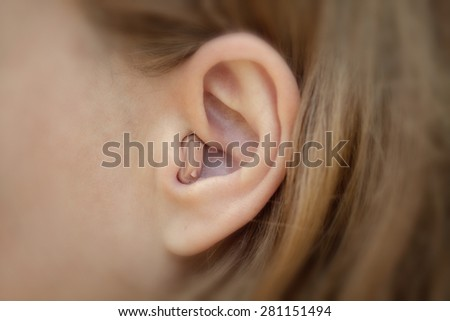 Hearing aid in your ear close-up. Modern equipment in medicine - stock photo