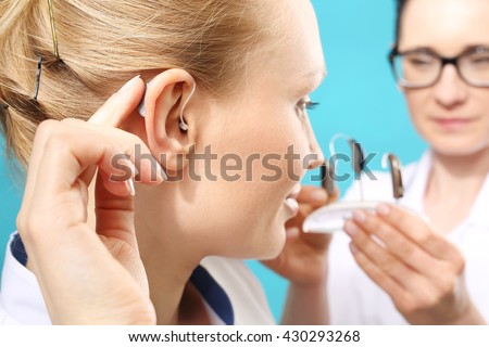 Hearing aid. The doctor assumes the woman hearing aid in your ear  - stock photo