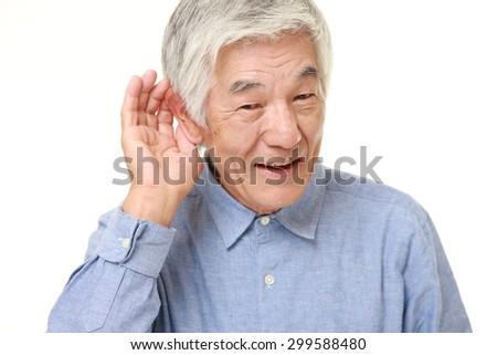 Hearing impaired senior Japanese man - stock photo