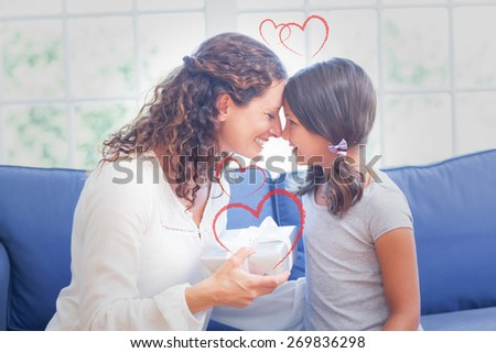 Heart against cute girl offering gift to her mother - stock photo