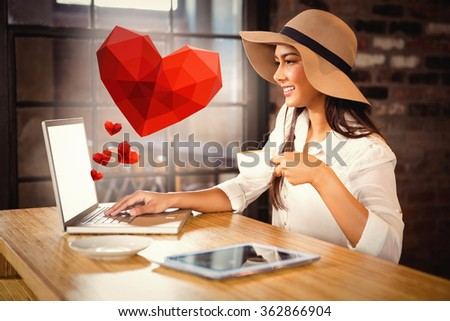 Heart against woman having coffee while using laptop in cafe - stock photo