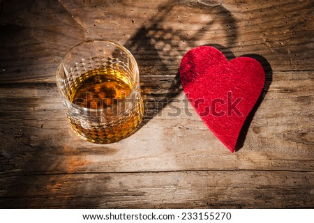 Heart and a glass of alcohol on a wooden table in the bar. i love whiskey - stock photo
