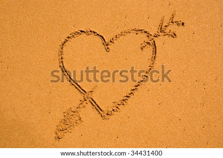 Heart and arrow in the sand - stock photo