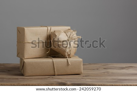 Heart and box wrapped in brown kraft paper on wooden table and grey background - stock photo