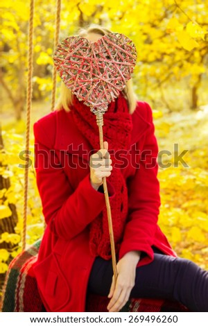 Heart as a sign of love in female hands, blurred background of autumn park. Decorative red heart in the foreground in the hands of a woman in a red coat. Yellow and red colors background is not focus. - stock photo