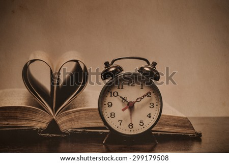 Heart book page with retro alarm clock, time concept- vintage effect style pictures - stock photo