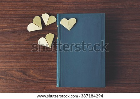 Heart bookmarks for book on wooden background - stock photo