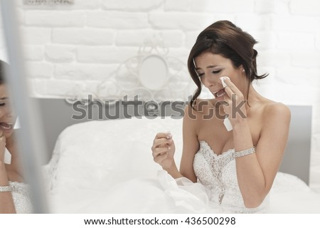 Heart-broken bride holding engagement ring, crying on wedding-day.