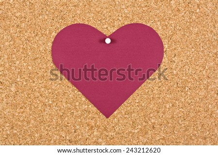 Heart button attached to corkboard - stock photo
