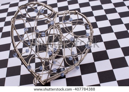 Heart cage on a checked background - stock photo