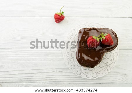 Heart cake. Pieces of chocolate cake with fresh strawberry on wooden background. Top view. - stock photo