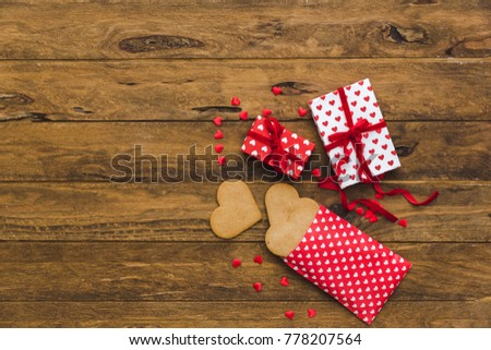 Heart cookies and gift boxes over wooden background. Top view. Copy space. Background for holidays: Birthday, Valentines day, Christmas, New Year