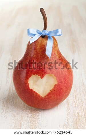 Heart cut out pear with bow on wooden background - stock photo