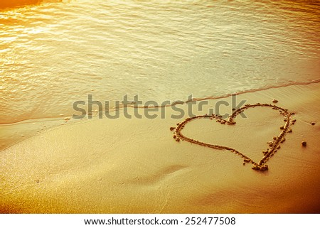 heart draw on sand beach under sunset and warm light. abstract background love summer on the beach. - stock photo