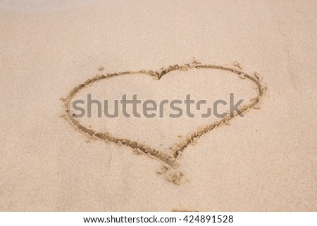 Heart drawing in the sand on a beach - stock photo