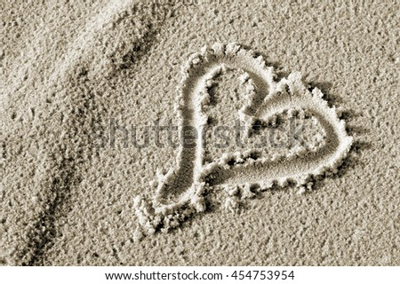 Heart drawn in the sand. - stock photo