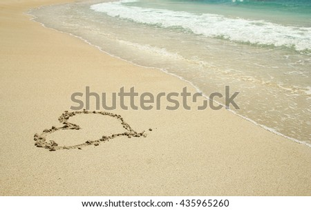 heart drawn in the sand on the beach - stock photo
