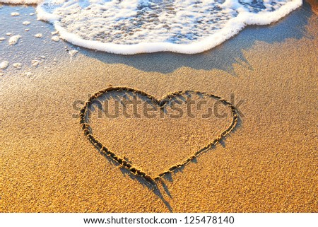 Heart drawn on the beach sand with sea foam and wave - stock photo