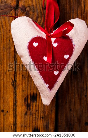 Heart fabric hand made on wooden background - stock photo