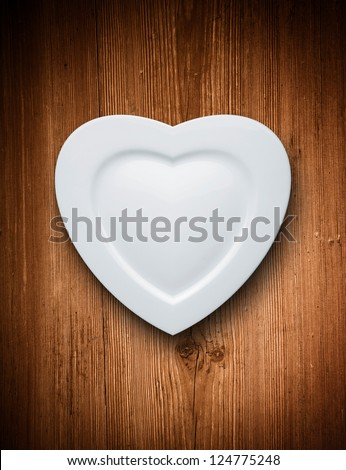 Heart form white plate on wood background - stock photo
