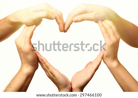 Heart formed by male and female hands on light background - stock photo