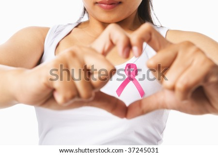 Heart framing from fingers on woman chest with pink badge to support breast cancer cause, PS: you can change the ribbon color to red to support AIDS cause as both using same symbol - stock photo