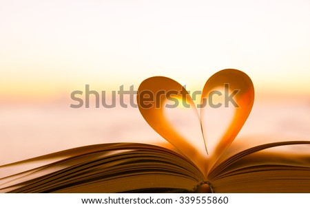 Heart from a book page against a beautiful sunset - stock photo