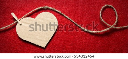 Heart from cardboard on rope with clothespin on red background with the gradient effect. Valentine's day, border design panoramic banner