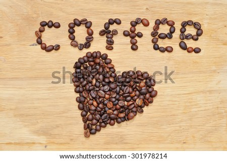 Heart from coffee grains on a wooden surface. - stock photo