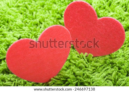 Heart from felt  on a green carpet - stock photo