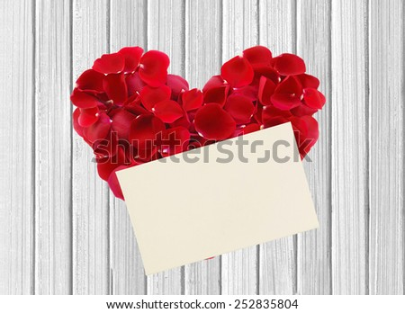 heart from red rose petals and paper on wooden table - stock photo