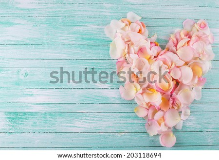 Heart from rose petals on aqua wooden background. Place for text. - stock photo