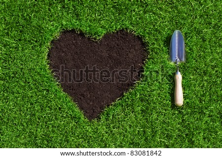heart from soil inside of green grass with a hand trowel beside