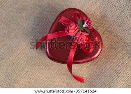Heart gift box on sack background - stock photo