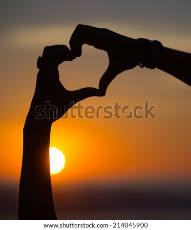heart hands shape at the sunset - stock photo
