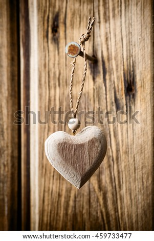 Heart hanging on nails, wooden texture background. Studio photo.