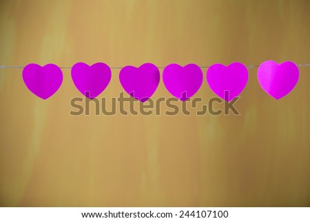 Heart hanging on the ropes, old yellow background. - stock photo